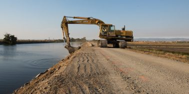 An excavator cuts material along a levee